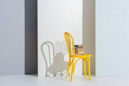 books on yellow chair on white and grey with copy space