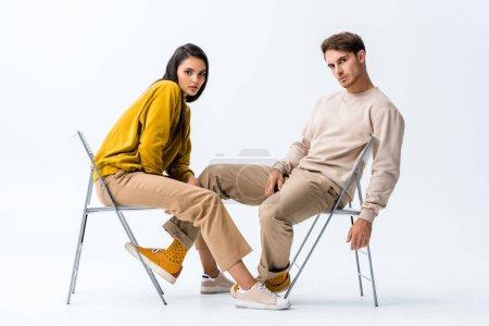 Photo pour Belle femme assise sur une chaise près de bel homme sur blanc - image libre de droit