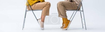 Photo for Panoramic shot of man and woman sitting on chairs on white - Royalty Free Image