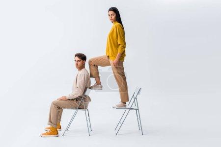 Photo pour Fille élégante debout sur la chaise près de bel homme assis sur blanc - image libre de droit