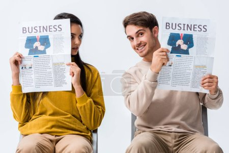 woman looking at happy man holding business newspaper isolated on white