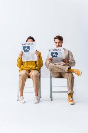 Photo pour Jeune femme et homme assis sur des chaises et lire des journaux d'affaires sur blanc - image libre de droit