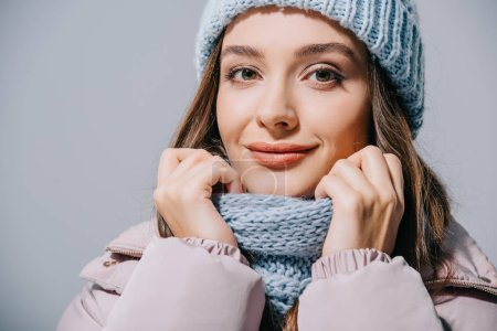 Photo for Beautiful smiling girl posing in coat, knitted hat and scarf, isolated on grey - Royalty Free Image