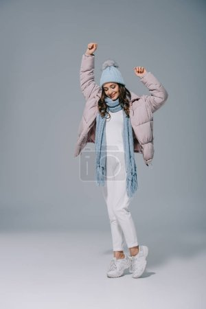 Photo for Beautiful girl dancing in warm coat, knitted hat and scarf on grey - Royalty Free Image