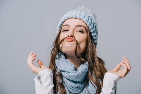 Photo pour Belle drôle fille en tricot chapeau et foulard faire de la moustache à partir de cheveux, isolé sur gris - image libre de droit