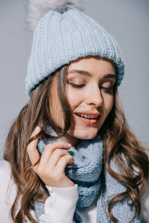Photo for Beautiful happy woman posing in blue knitted hat and scarf, isolated on grey - Royalty Free Image