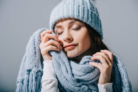 Photo pour Tender girl posing with closed eyes in blue knitted hat and scarf, isolated on grey - image libre de droit