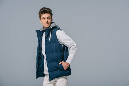 handsome stylish man posing in waistcoat, isolated on grey