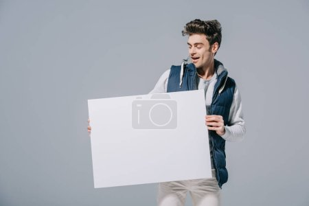 excited man in waistcoat posing with empty board, isolated on grey