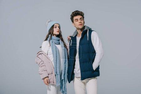 Photo pour Beau couple élégant posant en tenue d'hiver, isolé sur gris - image libre de droit