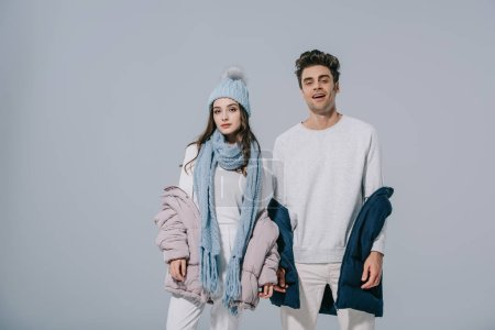 Photo for Fashionable young couple posing in winter outfit, isolated on grey - Royalty Free Image