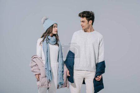 Photo for Beautiful stylish young couple posing in warm winter outfit, isolated on grey - Royalty Free Image