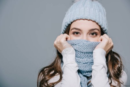 Photo pour Attractive woman posing in knitted hat and scarf, isolated on grey - image libre de droit