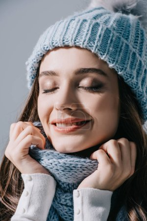 Photo pour Beautiful dreamy woman posing with closed eyes in knitted hat and scarf, isolated on grey - image libre de droit