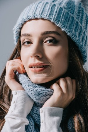 Photo for Beautiful woman posing in knitted hat and scarf, isolated on grey - Royalty Free Image