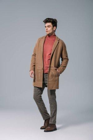 Photo pour Bel homme à la mode posant en manteau beige sur gris - image libre de droit