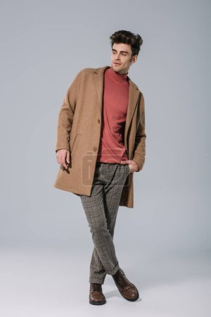 Photo for Handsome male model posing in stylish beige coat on grey - Royalty Free Image