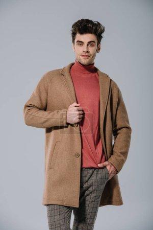 Photo pour Bel homme à la mode posant en manteau beige, isolé sur gris - image libre de droit