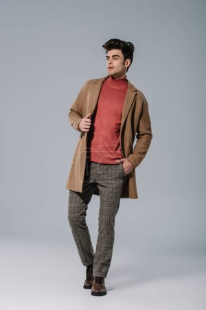 Photo for Fashionable young man posing in beige coat on grey - Royalty Free Image