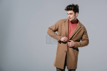 Photo for Fashionable man posing in trendy coat, isolated on grey - Royalty Free Image