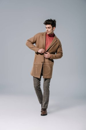Photo for Fashionable man posing in beige autumn coat on grey - Royalty Free Image