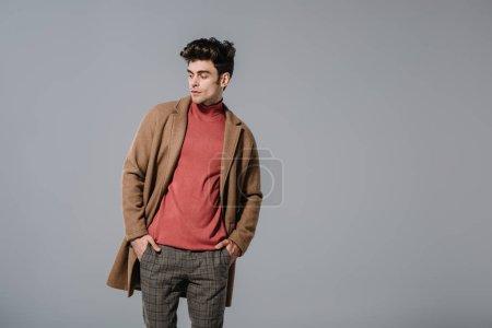 Photo pour Homme à la mode posant en manteau d'automne, isolé sur gris - image libre de droit