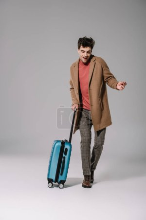 Photo for Happy stylish man in beige coat dancing with travel bag on grey - Royalty Free Image