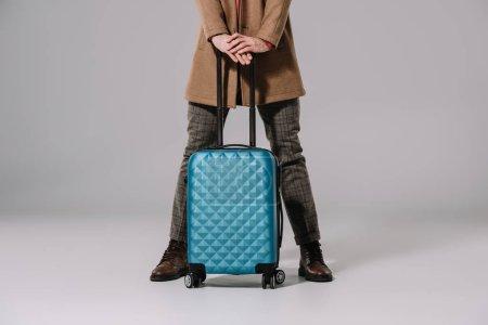 Photo pour Crochet vue de l'homme posant avec son sac de voyage sur fond gris - image libre de droit