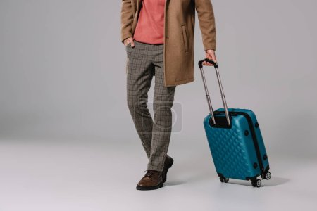 cropped view of man posing with baggage for travel on grey