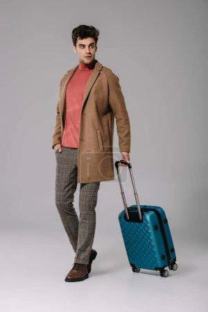 Photo pour Homme élégant posant en manteau beige avec sac de voyage sur gris - image libre de droit