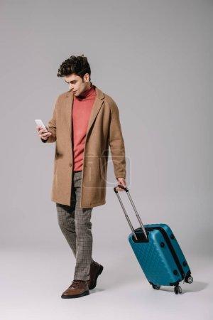 Foto de Elegante hombre en la cubierta de beige con bolsa de viaje usando smartphone en gris. - Imagen libre de derechos