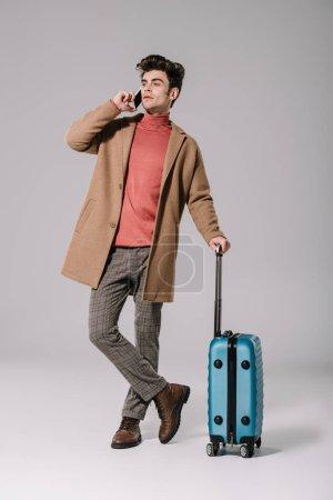 Foto de A la moda hombre en el abrigo beige hablando en teléfono inteligente y teniendo bolsas de viaje en gris. - Imagen libre de derechos