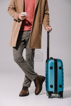 Photo for Cropped view of stylish man standing with travel bag and smartphone on grey - Royalty Free Image