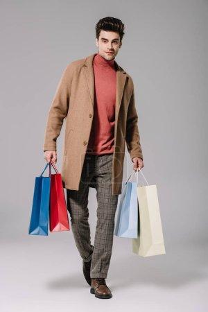 Foto de Con estilo en abrigo de beige y bolsas de la compra en gris - Imagen libre de derechos