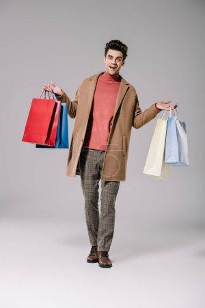 Photo pour Bel homme souriant en manteau beige marchant avec des sacs à provisions sur gris - image libre de droit