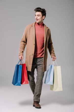 Photo pour Happy-fashionable man in beige coat walking with shopping bags on grey - image libre de droit