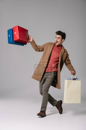 Photo for Excited stylish man in beige coat walking with shopping bags on grey - Royalty Free Image