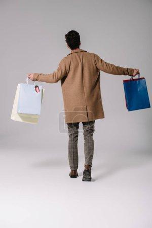 Photo pour Vue arrière de l'homme élégant en manteau beige marchant avec des sacs à provisions sur gris - image libre de droit