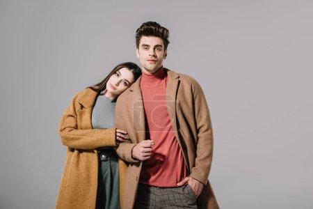 Photo pour Beau couple élégant blotti dans des manteaux beiges, isolé sur gris - image libre de droit