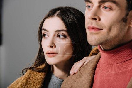 Photo pour Portrait de couple stylisé posant en manteau beige, isolé sur gris - image libre de droit