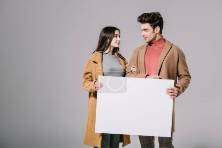 Photo for Beautiful stylish couple in beige coats posing with empty board, isolated on grey - Royalty Free Image