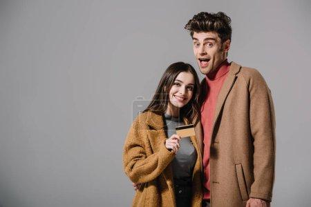 Photo pour Couple excité en manteaux beige tenant la carte de crédit isolé sur gris - image libre de droit