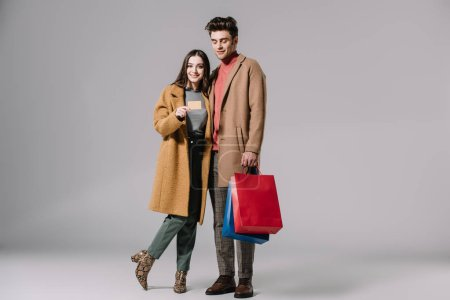 Photo for Beautiful couple in beige coats posing with shopping bags and credit card on grey - Royalty Free Image