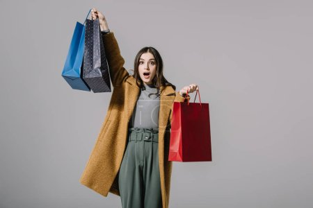 Photo for Beautiful shocked girl in beige coat holding shopping bags, isolated on grey - Royalty Free Image