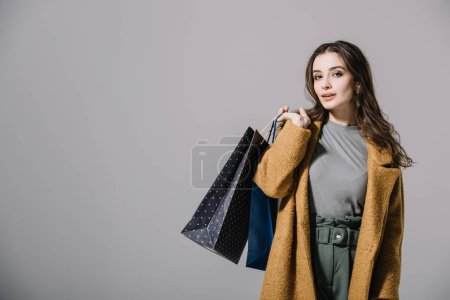 Photo for Fashionable lady in beige coat holding shopping bags, isolated on grey - Royalty Free Image