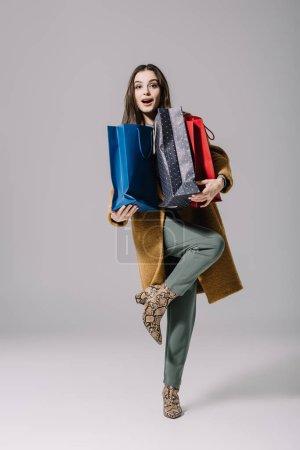 Photo pour Femme surprise à la mode en manteau beige tenant des sacs à provisions sur gris - image libre de droit