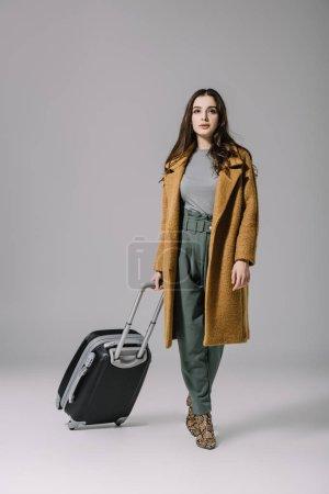 Foto de Hermosa mujer elegante en la cubierta de beige caminando con bolsa de viaje en gris. - Imagen libre de derechos
