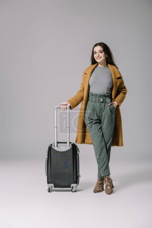 Photo for Beautiful smiling girl in beige coat posing with travel bag on grey - Royalty Free Image