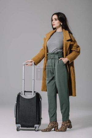 Photo pour Belle femme en manteau beige posant avec valise sur gris - image libre de droit