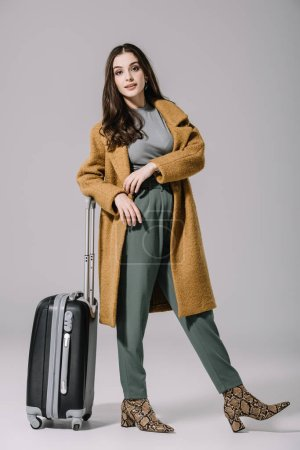 Photo for Beautiful woman in beige coat posing with travel bag on grey - Royalty Free Image